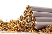 Cigarettes in loose tobacco, close up against white — Stock Photo