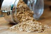 Rolled oats falling out of a glass jar — Stock Photo