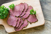 Cold beef  in slices on a wooden board, view from above — Stock Photo