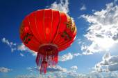 Chinese red lantern with character for happiness in front of blue sky with white clouds, copyspace — Stockfoto