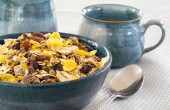 Granola in a blue bowl, ceramic mugs in the background — Stock Photo