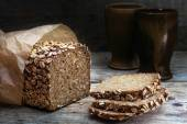 Wholegrain bread with seeds on weathered wood, dark background — Stock Photo