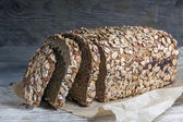 Dark bread loaf with whole grain and seeds on an old wooden boar — Stock Photo