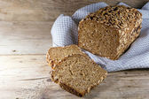 Bread loaf and slices on rustic wood, copy space — Stock Photo