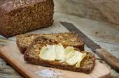Dark rye bread with seeds, butter and salt on rustic wood — Stockfoto