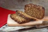 Fresh dark rye bread with whole grain on rustic wood — Stock Photo