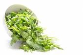 Rocket salad leaves, rucola or arugula, falling from a ceramic b — ストック写真