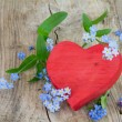 Red wooden heart shape with forgett-me-not flowerd on old wood — Stock Photo #71695899
