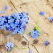 Forget-me-not flowers in a silver heart shape on rustic wood — Stock Photo #71696001