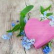 Pink heart shape made of wood with forget-me-not flowers on a wo — Stock Photo #71696345