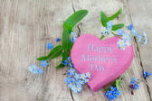 Pink wooden heart shape with text happy mothers day and forgetme — Stock Photo