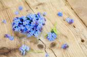 Forget-me-not flowers in a silver heart shape on rustic wood — Stock Photo