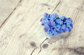 Heart shape with forget-me-not flowers on  rustic wood — Stock Photo