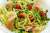 Spaghetti with green pesto, prosciutto and tomatoes — 图库照片