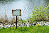 Blank rusty signboard on a river bank — Stock Photo