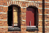 Boarded up windows in an old brick wall — Stock Photo