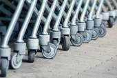 Wheels of shopping carts in a diagonal row, selected focus — Foto de Stock