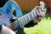 Man making music by playing guitar, detail with selected focus o — Stock Photo