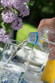 Man's hand pouring water from a bottle into a glass on a garden  — Stock Photo