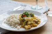 Yellow vegetable curry with rice on a white plate — Stock Photo