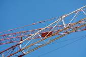 Crane arms diagonally against the blue sky — Stock Photo