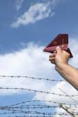 Man's hand holding his passport as a paper airplane  over a barb — Stock Photo