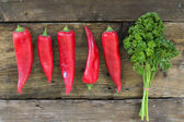 Red sweet pointed peppers in a row and parsley on rustic wood — Stock Photo