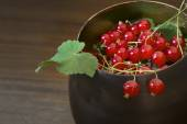 Red currants and leaves in a metal  bowl against brown backgroun — Stock Photo