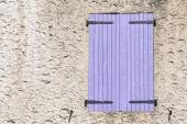 Closed window shutters of purple wood in a rough-plastered wall — Stock Photo