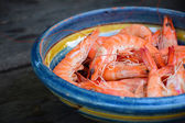 Shrimps in a earthenware dish on a rustic woodem table — Stock Photo