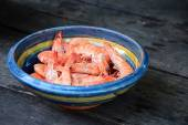 Boiled tiger shrimps in a earthenware bowl on rustic dark wood — Stock Photo