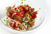 Tomato salad with onion rings and herbs in a glass bowl — Stock Photo