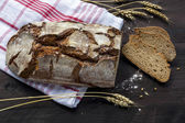 Rustic bread loaf and slices with wheat ears on a dark wooden ta — Stock Photo