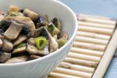 Mushroom vegetable dish in a white bowl on a bamboo mat, closeup — Stock Photo