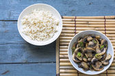Mushroom vegetables and cooked rice in bowls on a bamboo mat and — Stock Photo