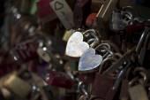 Silver love locks in heart shape on a bridge railing — Stock Photo