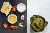 Cooked artichoke with dips and ingredients, background half dark — Stock Photo