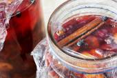 Preserved red fruits with spices in glass jars — Stock Photo
