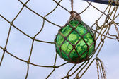 Glass fishing float ball with rope knots hanging in a fishing n — Stock Photo