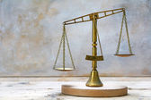 Vintage scales of justice out of balance — Stock Photo