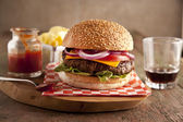 Classic deluxe cheeseburger with lettuce, onions, tomato and pickles on a sesame seed bun — Stock Photo