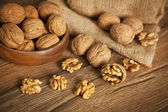 Walnut kernels and whole walnuts on rustic old wooden table — Stock Photo