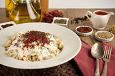 Turkish Manti manlama on plate with red pepper, tomatoes sauce, yogurt and mint — Stock Photo