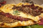 Homemade traditional Turkish meal pizza pide stuffed with meat, cheese, pastirma and sausage — Stock Photo