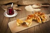Typical turkish owen product cheese pogaca with wood plate and black tea — Stock Photo
