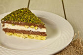 Pistachio cheesecake, mousse cake with nuts decoration on a white plate — Stock Photo