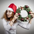 Tired sleepy woman waking up happy with xmas santa hat and christmas flowers — Stock Photo #57697461