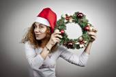 Tired sleepy woman waking up happy with xmas santa hat and christmas flowers — Stock Photo