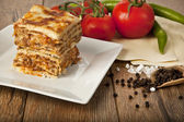 A Piece of Italian Lasagna Bolonese on a square plate — Stock Photo