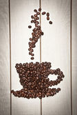Cup of coffee shape with coffee beans — Stock Photo